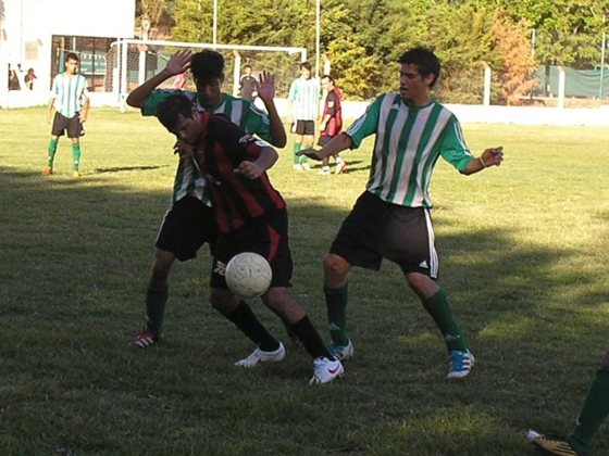 La figura de la cancha, Sebastián Benítez, cuida el balón ante dos rivales que lo rodean.